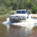 4x4 vehicle driving through river