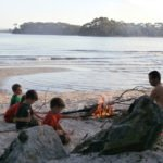 Children sitting around campfire on beach