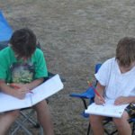 Children doing written activities on family camping trip