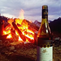 Bottle of wine by campfire at sunset